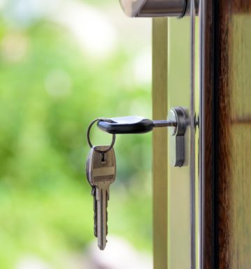 Keys in the door of a house, representing a newly purchased home