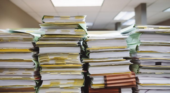 Stacks of paper files representing litigation resuming in Ontario