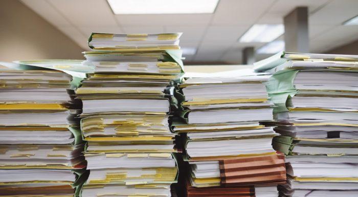 Stacks of paper files representing litigation resuming in Ontario